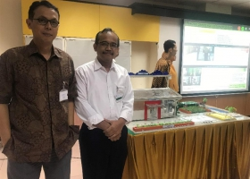 Mr.Harris Fadillah of UNIDO and Mr.Wiharja of BPPT, as a member of AGC assessor pictured with background of participant's presentation and their factory miniature.